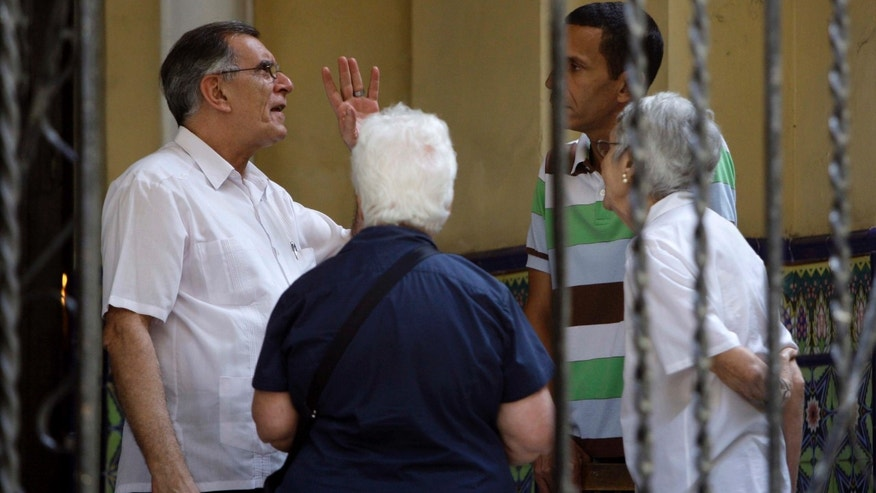 Roberto Betancourt, priest at the Virgin of Charity of Cobre Catholic church, left, speaks with unidentified people outside the church in Havana, Cuba, Thursday March 15, 2012. A group of Cuban dissidents who have occupied the church for two days are no longer demanding an audience with Pope Benedict XVI when he visits this month, but vowed Thursday to continue their protest. The dissidents say they are now asking the pontiff to mediate a list of their grievances with the Cuban government.