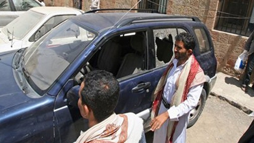 Mar. 18, 2012: Yemenis gather around a damaged vehicle purported to belong to an American teacher shot by gunmen in Taiz, Yemen.