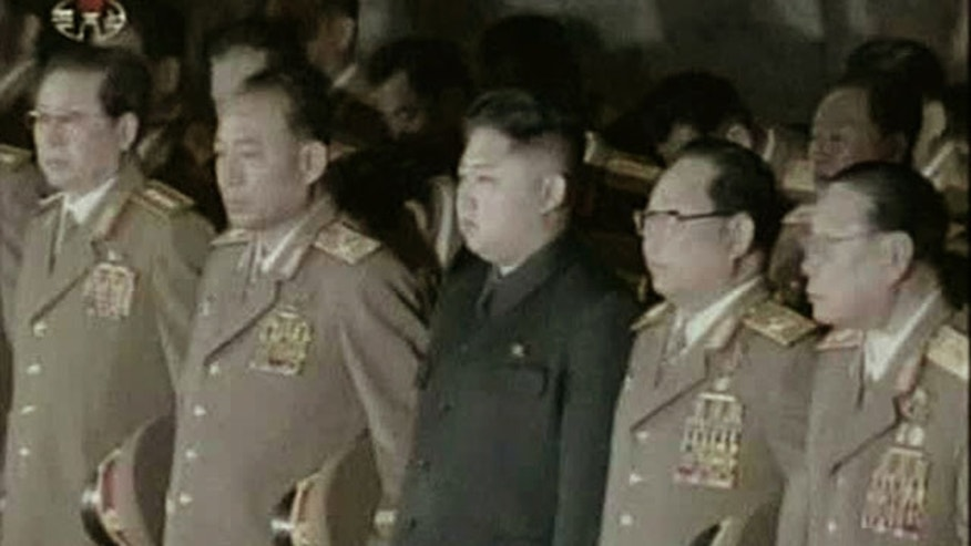 Dec. 24, 2011: Kim Jong Un, center, North Korean leader Kim Jong Il's youngest known son and successor, with military officials, stand in front of his father's body displayed in a glass coffin, not in photo, at Kumsusan Memorial Palace in Pyongyang, North Korea.
