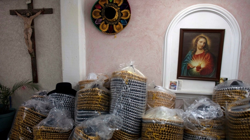 In this Feb. 29, 2012 photo, packaged Mexican sombreros stand next to religious images at the sombrero shop of Maria de la Luz Yepez, not shown, who is preparing three Mexican style sombreros to give as presents to Pope Benedict XVI, in the town of San Francisco del Rincon, near León, Mexico. The visit of Pope Benedict XVI, his first to Spanish-speaking Latin America, begins on March 23 in Mexico's central state of Guanajuato, where he will spend three days and give an outdoor Mass before heading to Cuba on March 26.  (AP Photo/Dario Lopez-Mills)