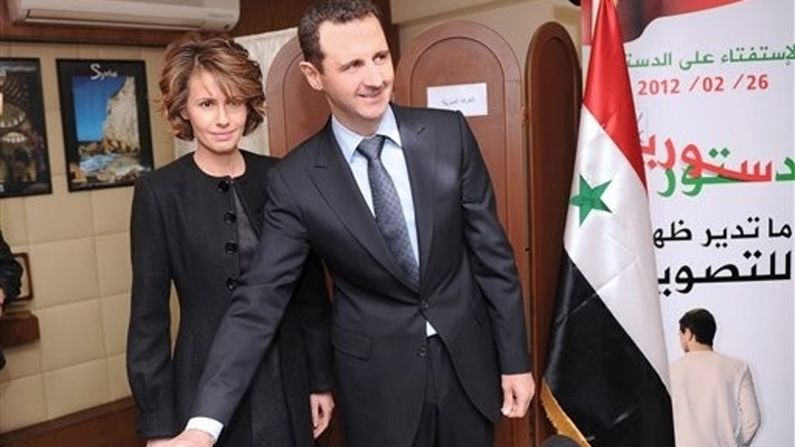 Feb. 26, 2012: In this photo released by the Syrian official news agency SANA, Syrian President Bashar Assad casts his ballot next to his wife Asma at a polling station during a referendum on the new constitution, in Damascus, Syria.