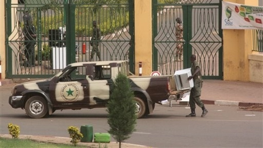 March 22, 2012: A soldier loads an appliance into a truck outside the gates of the compound containing government ministries in Bamako, Mali. Drunk soldiers looted Mali's presidential palace hours after they declared a coup on Thursday, suspending the constitution and dissolving the institutions of one of the few established democracies in this troubled corner of Africa.