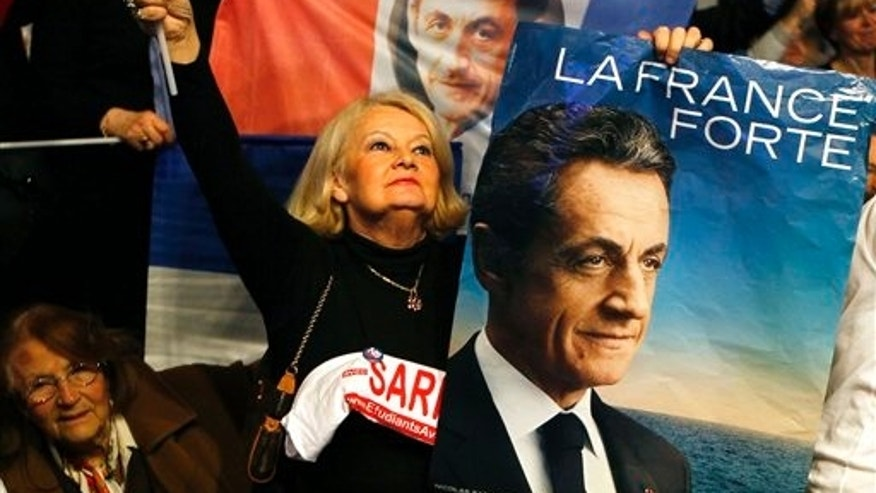March 11: A supporter holds portrait of France's president and candidate for the upcoming re-election, Nicolas Sarkozy during a meeting in Villepinte, north of Paris, France, as part of his electoral campaign.