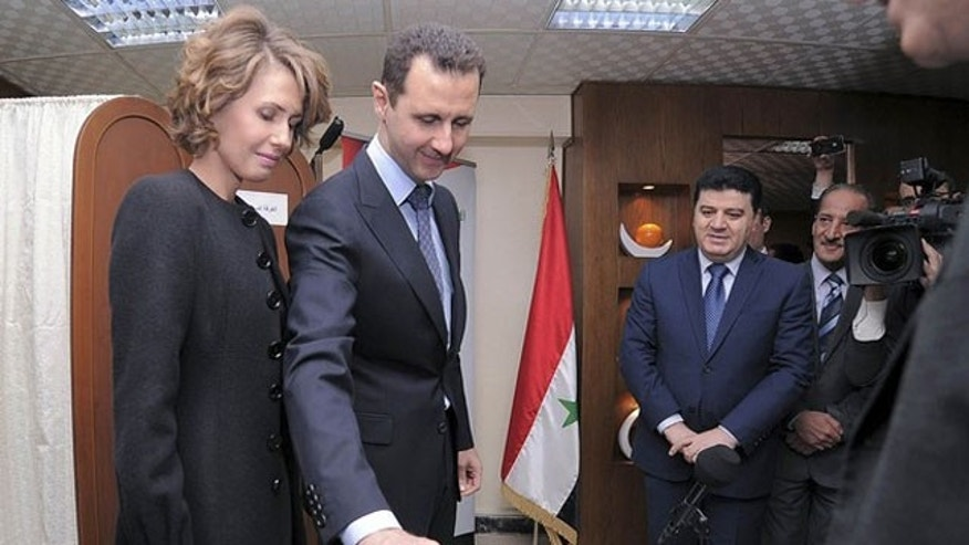 February 26, 2012: Syria's President Bashar al-Assad and his wife Asma vote during a referendum on a new constitution at a polling station in a Syrian TV station building in Damascus.