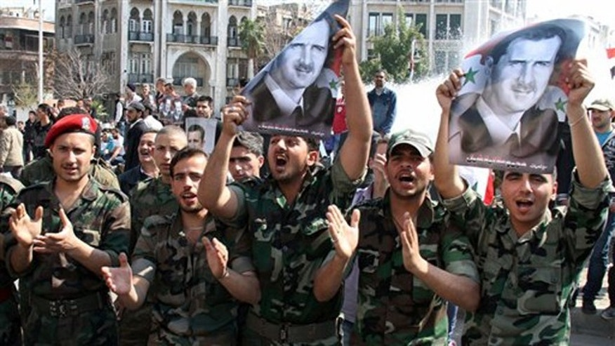 March 23, 2012: Syrian Army soldiers shout slogans and hold up portraits of Syrian President Bashar Assad, during a pro-regime rally in Damascus, Syria.