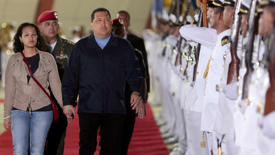 In this photo released by Miraflores Press Office, Venezuela's President Hugo Chávez, center, and his daughter Rosa Virginia, left, review the honor guard prior to their departure to Havana, at the Simón Bolívar airport in Maiquetía, Venezuela, Saturday. (AP Photo/Miraflores Press Office/Francisco Batista)