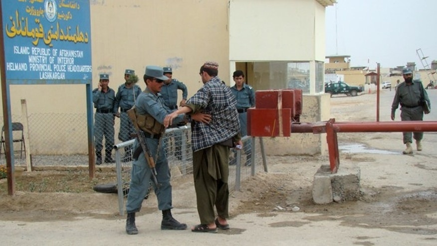 March 26, 2012: An Afghan policeman checks a man entering the provincial police station near the main gate of a joint civilian-military base where two British soldiers part of the NATO forces were killed in Lashkar Gah, Helmand province, south of Kabul, Afghanistan.