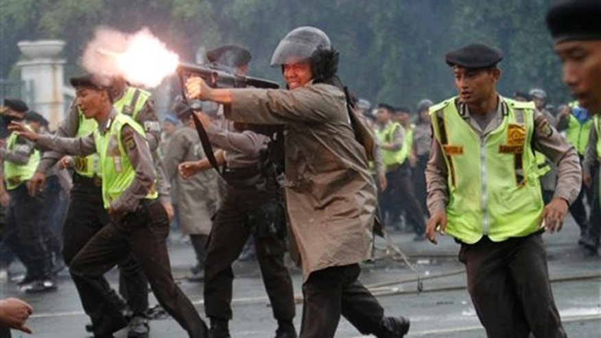 March 27, 2012: An Indonesian police officer fires a tear gas launcher to disperse student protesters during a protest against the government's plan to raise fuel prices in Jakarta, Indonesia.