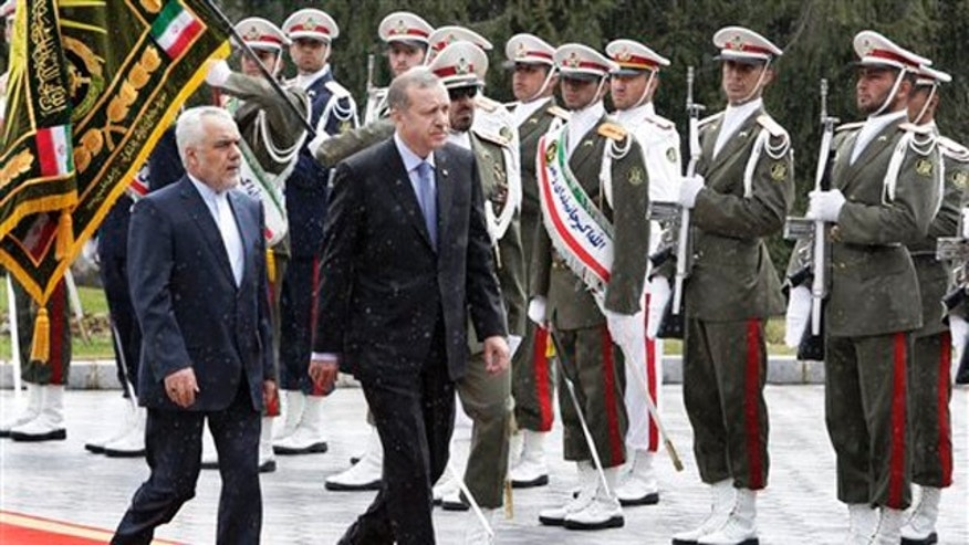 March 28, 2012: Turkish Prime Minister, Recep Tayyip Erdogan, right, is accompanied by Iranian Vice-President Mohammad Reza Rahimi, left, during an official welcoming ceremony in Tehran, Iran.