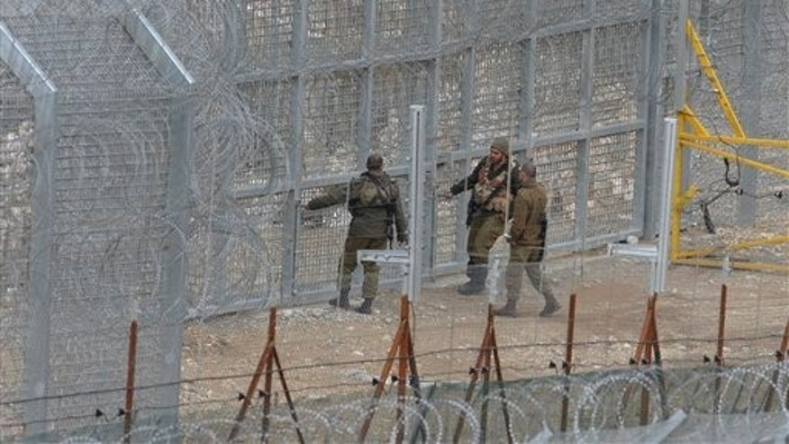 March 29: Israeli soldiers stand on the border fence between Majdal Shams in the Golan Heights, and Syria, as security is tightened ahead of Land Day.