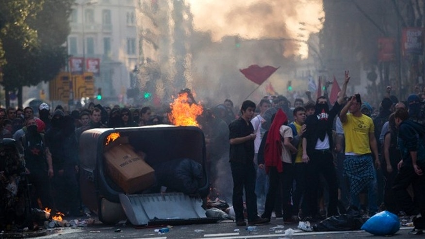 March 29, 2012: Demonstrators are seen next to burnt trash containers during clashes with police during a general strike in Barcelona, Spain.