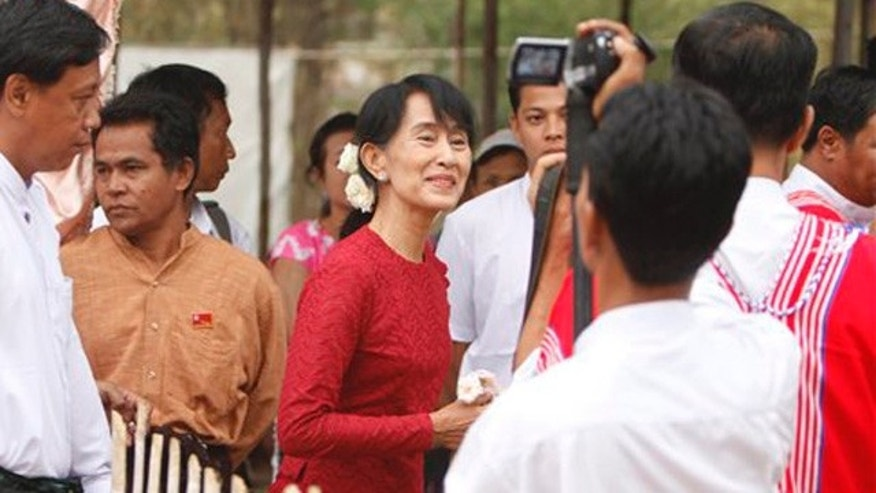 April 1, 2012: Burma's National League for Democracy party leader Aung San Suu Kyi, center, heads towards a polling station at Wah Thin Kha village in Yangon, Burma.