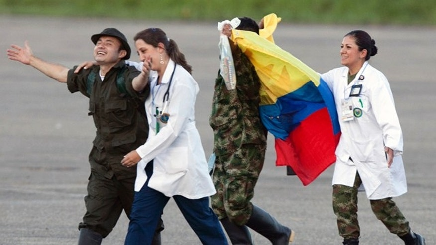 April 2, 2012: Accompanied by medical personnel, police sergeant Cesar Augusto Lasso, left, and army sergeant Luis Alfredo Moreno, third from left, gesture upon their arrival to an airport after being released by the Revolutionary Armed Forces of Colombia, or FARC, in Villavicencio Colombia.
