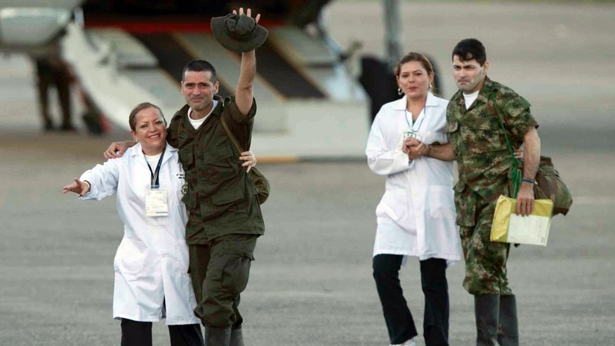 Former hostages army sergeant Luis Alfonso Beltran, right, and police officer Jorge Trujillo Solarte, second from left, arrive to an airport after being released by the Revolutionary Armed Forces of Colombia, or FARC, in Villavicencio Colombia, Monday, April 2, 2012. Colombia's main rebel group on Monday freed what it says were its last 10 soldier and police captives, all of whom had been held in jungle prisons for at least 12 years. (AP Photo/Fernando Vergara)