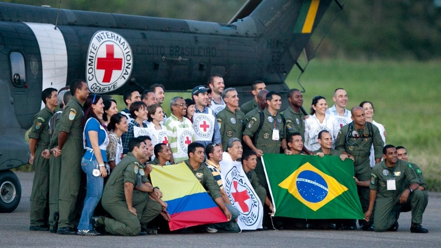 Crew members of a Brazilian army helicopter and International Red Cross members, pose for pictures after participating in a rescue operation of hostages released by the Revolutionary Armed Forces of Colombia, or FARC, in Villavicencio, Colombia, Monday, April 2, 2012. Colombia's main rebel group on Monday freed what it says were its last 10 soldier and police captives, all of whom had been held in jungle prisons for at least 12 years. (AP Photo/Fernando Vergara)