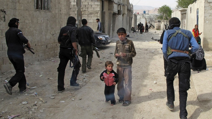 April 1, 2012: Syrian boys watch Free Syrian Army fighters move through a neighborhood of Damascus, Syria.