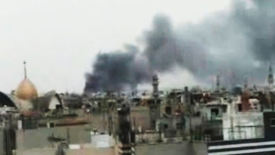 Monday, March 26: This image made from amateur video and released by Shaam News Network purports to show smoke rising from buildings in Homs, Syria. Syrian troops shelled rebel-held neighborhoods in the central city of Homs on Monday with at least five people seriously wounded.