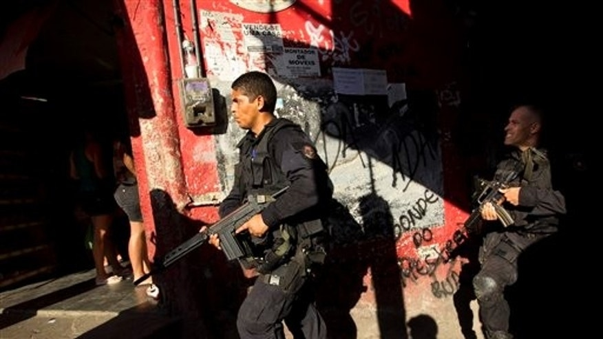 April 4, 2012: Police officers belonging to the BOPE (Special Police Operations Battalion) unit, patrol the Rocinha slum in Rio de Janeiro, Brazil.