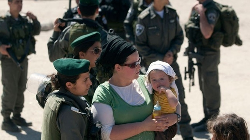 Apr. 4, 2012: A Jewish settler is stopped at a checkpoint manned by Israeli border police near a house illegally occupied by settlers in the West Bank city of Hebron.