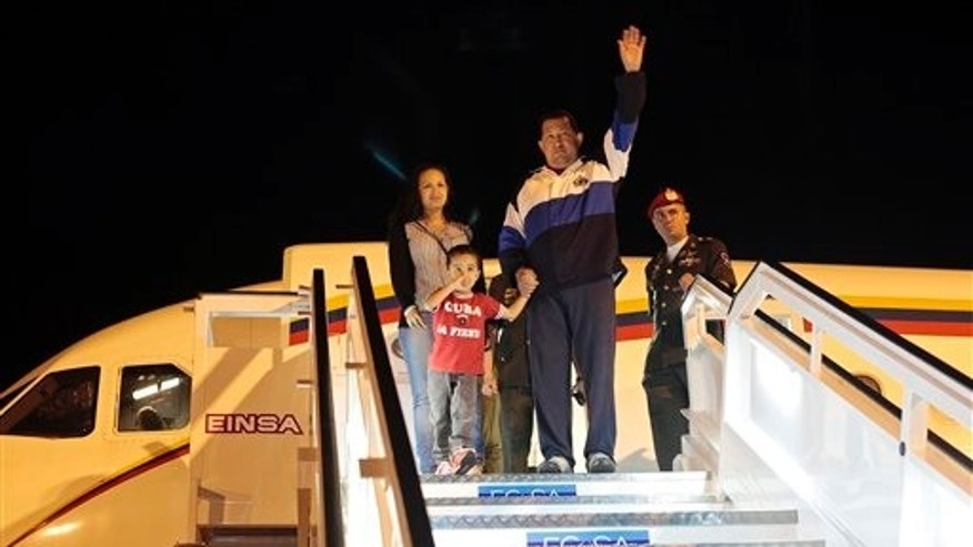 March 31, 2012: Venezuela's President Hugo Chavez waves as he stands with his daughter Rosa Virginia and his grandson Jorge upon arrival to the airport in Havana, Cuba.
