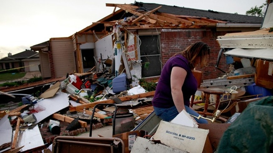April 03, 2012:  April Bridges searches through the remains of a house she at when it was destroyed by a tornado in Arlington, Texas. Multiple tornadoes touched down across the Dallas/Fort Worth area causing extensive damage.