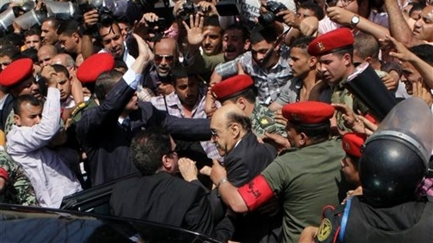 April 8: Former Egyptian Vice President Omar Suleiman, center, is escorted by military police as he prepares to submit his candidacy papers at the Higher Presidential Elections Commission, in Cairo, Egypt.