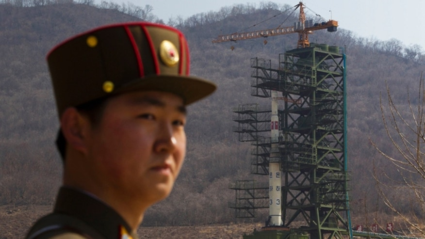 April 8: A North Korean soldier stands in front of the country's Unha-3 rocket, slated for liftoff between April 12-16, at a launching site in Tongchang-ri, North Korea.