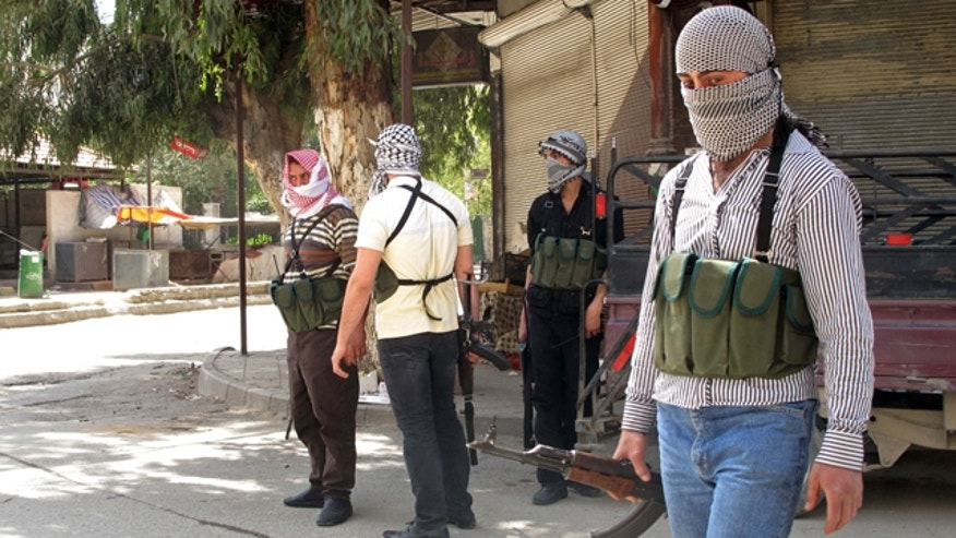April 6: Free Syrian Army fighters gather on a corner during fighting with Syrian troops in a suburb of Damascus, Syria.