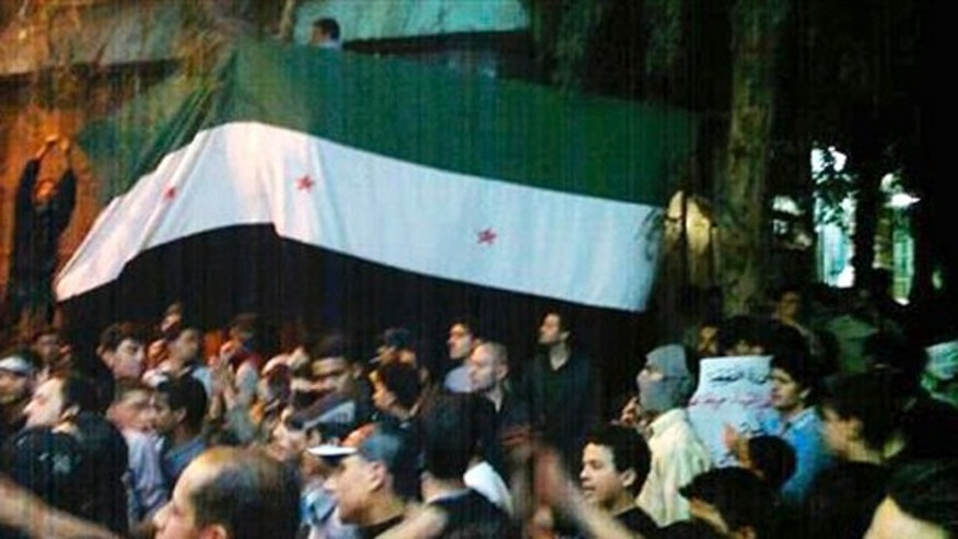 April 10, 2012: In this image provided by the Local Coordination Committees in Syria, Syrians hold the Syrian revolutionary flag aloft during a demonstration in Damascus, Syria.