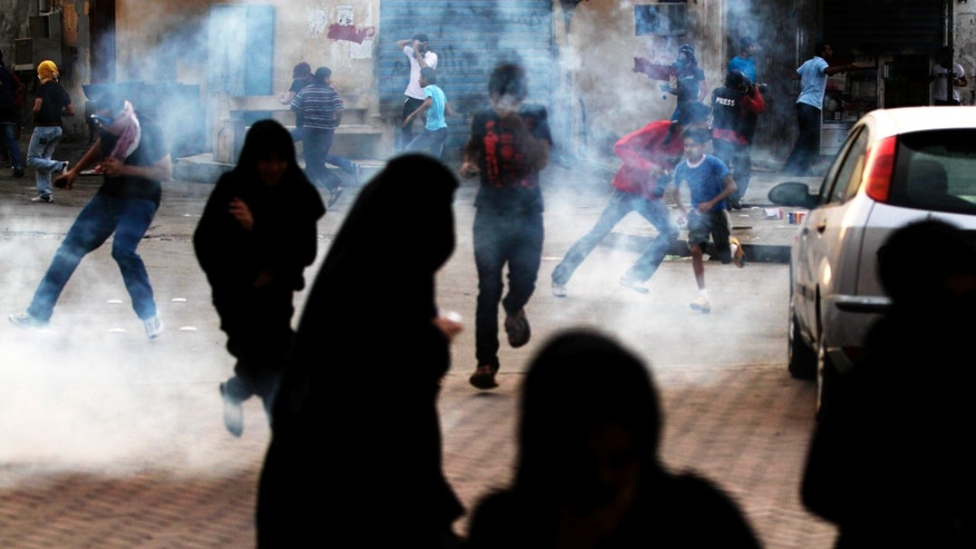 April 10, 2012: Bahraini anti-government protesters run from tear gas fired by riot police in Bilad al-Qadeem, Bahrain, on the edge of the capital of Manama, where demonstrators gathered in support of jailed Bahraini  political leaders.