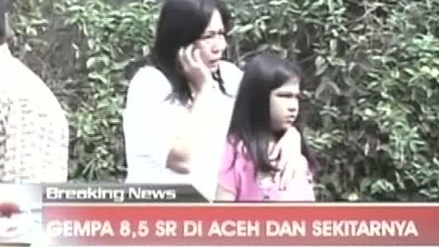 April 11, 2012: In this image made from Indonesian television TV One, a woman hugging a girl uses a mobile phone shortly after they ran out from a building when a strong earthquake hit in Aceh in Indonesia.