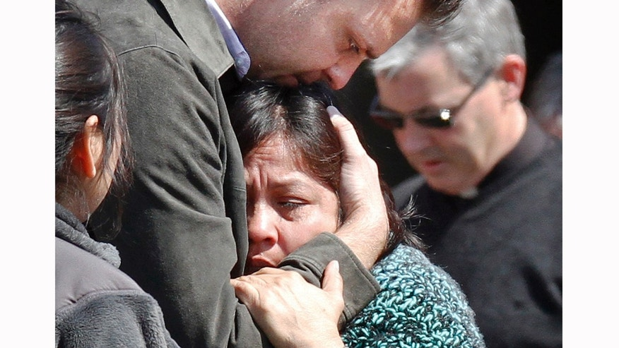 Luzmila Garcia, center, is consoled after the body of her missing son, Boston College student Franco Garcia, was recovered at Chestnut Hill Reservoir in Boston, Wednesday, April 11, 2012.  Franco Garcia disappeared Feb. 22 after leaving a popular bar near the college. (AP Photo/Michael Dwyer)