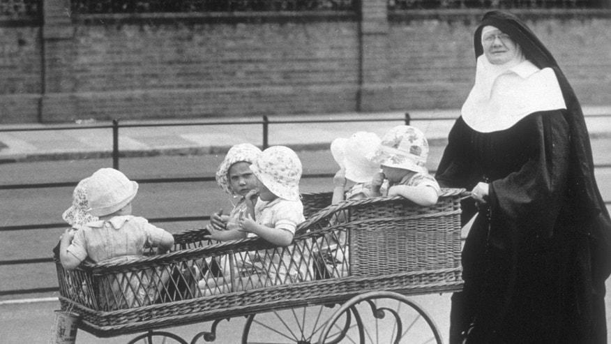 circa 1937:  A Sister of Mercy nun pushing six babies in a six-seater pram along Clacton Promenade.  (Photo by Fox Photos/Getty Images)