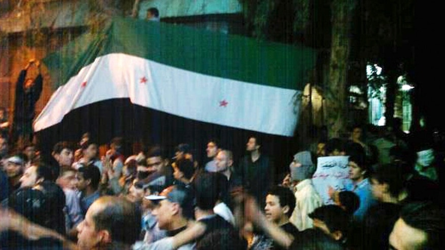 April 10: In this image provided by the Local Coordination Committees in Syria, Syrians hold the Syrian revolutionary flag aloft during a demonstration in Damascus, Syria.