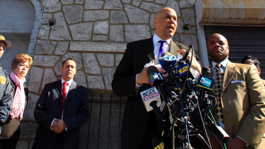 Newark Mayor Cory Booker talks about the fire in his next door neighbor's house in which he members of his security detail, including Alex Rodriguez, third from left, rescued residents from the burning building.