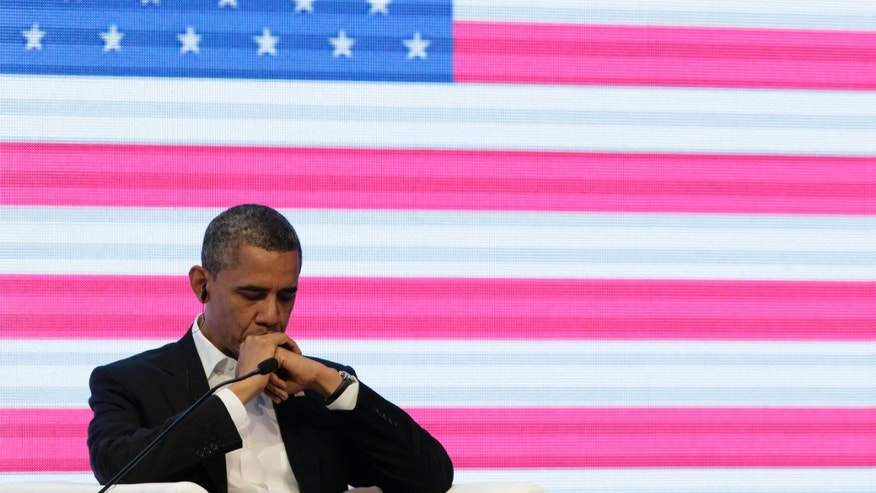April 14, 2012: President Barack Obama sits in front of a large video screen displaying an image of a U.S. national flag during a three-way conversation with Brazil's President Dilma Rousseff and Colombia's President Juan Manuel Santos, not pictured, at the CEO Summit of the Americas, in Cartagena, Colombia.