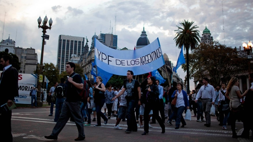 "People, carring a banner with the colors of the Argentine flag that reads in Spanish ""YPF belongs to the Argentines,"" demonstrate in support of a bill proposed by Argentina's President Cristina Fernández de Kirchner outside the government house in Buenos Aires, Argentina, Monday. (AP Photo/Natacha Pisarenko)"