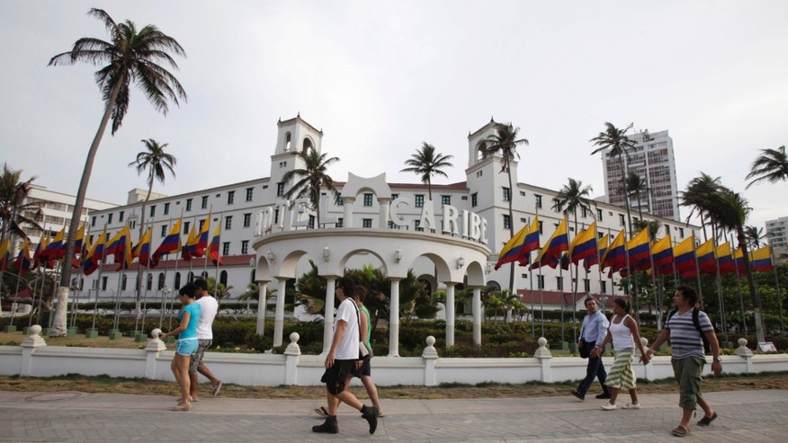 People walk past Hotel El Caribe in Cartagena, Colombia, Saturday April 14, 2012. (AP Photo/Fernando Vergara)