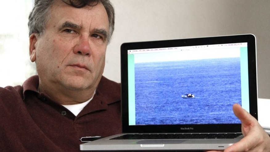 Jeff Gilligan, who was a passenger on the American-based cruise ship Star Princess  last March, holds a laptop in Portland, Ore., Thursday, April 19, 2012,  with the photo he took of a fishing vessel adrift in the Pacific Ocean off the Galapagos Islands while on the cruise.(AP Photo/Jeff Gilligan)