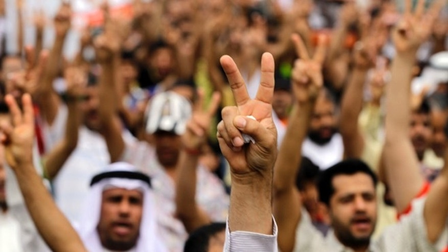 April 21, 2012: Bahraini anti-government protesters gesture as they march in Diraz, Bahrain, west of the capital of Manama.