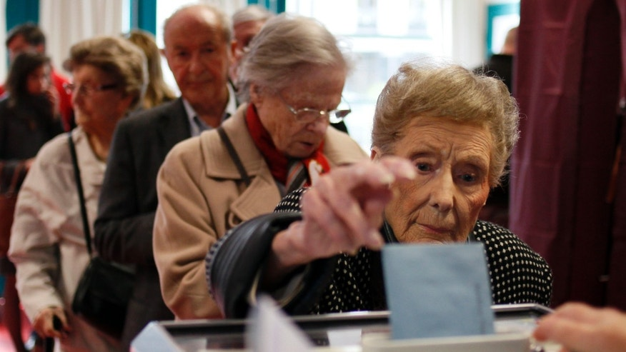 April 22, 2012: A woman casts her ballot during the first round of the French elections in Lille, northern France.