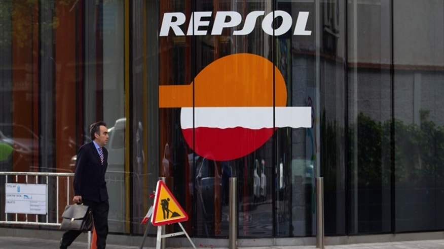 A man walks past a Repsol gas station in Madrid, Wednesday April 18, 2012.  (AP Photo/Paul White)