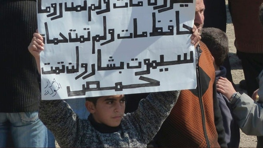 March 2: A boy holds up a placard during a demonstration against Syria's Assad near the city of Homs that reads: 'Nero died, Rome did not die, Hafez died, Hama did not die, Bashar will die, Homs will not die.'