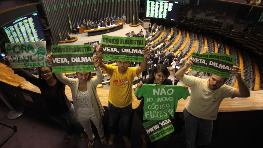 "Environmentalists hold up protest signs that read in Portuguese ""Veto Dilma,"" ""Mourning for the Forest"" and ""No to the new forest lawâ during a session by Chamber of Deputies who are expected to vote on a new forest law in Brasilia, Brazil, Wednesday, April 25, 2012.  Environmentalists say that any changes made to Brazil's benchmark environmental laws will damage the Amazon and other areas. (AP Photo/Eraldo Peres)"