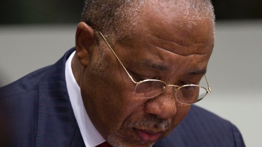April 26, 2012: Former Liberian President Charles Taylor takes notes as he waits for the start of a hearing to deliver verdict in the court room of the Special Court for Sierra Leone in Leidschendam, near The Hague, Netherlands.