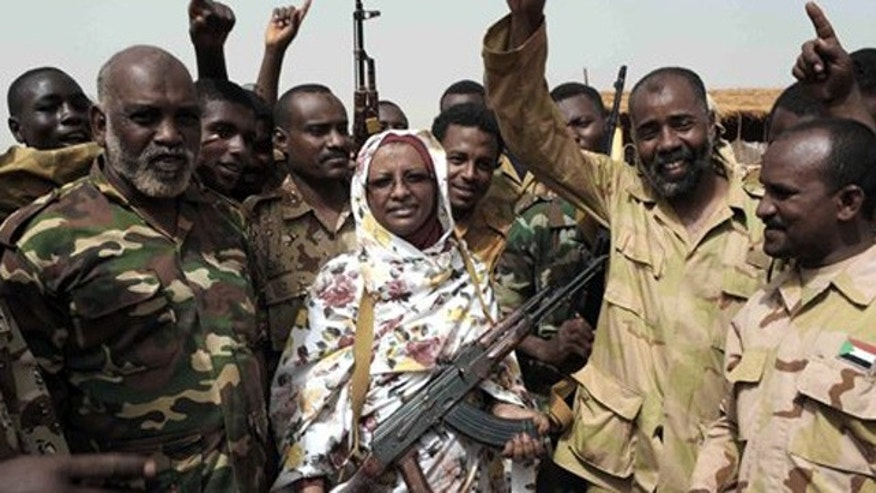 April 24, 2012: Sudanese state Minister of Information Sana Hamad poses for a photo with Sudanese armed forces at the oil-rich border town of Heglig, Sudan.