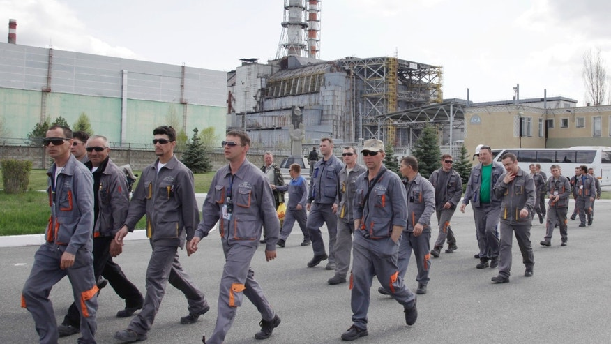 Thursday: Construction workers pass by the damaged reactor at the Chernobyl nuclear power plant in Chernobyl, Ukraine.