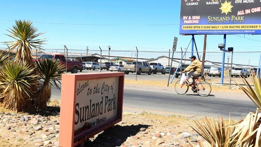 March 22: A lone bicyclist pedals past a welcome sign as he enters Sunland Park, N.M. Scandal in this small border town is nothing new. (AP Photo/Ross D. Franklin)