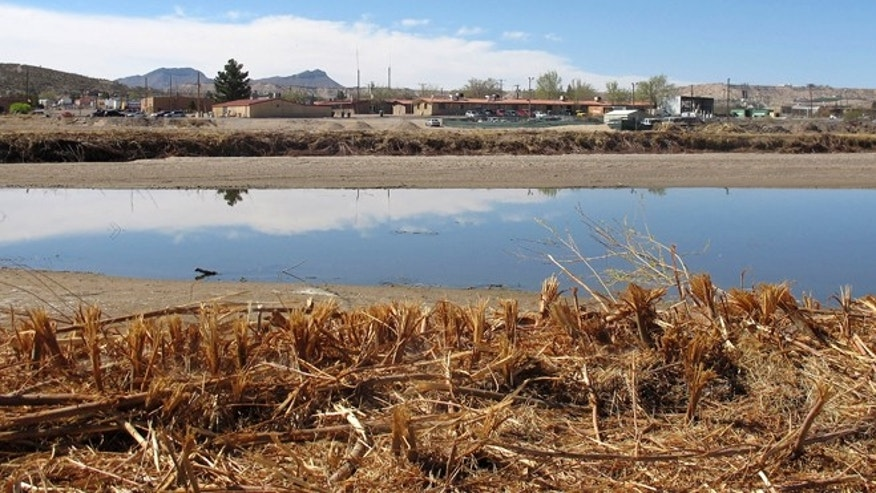 In this March 13, 2012 photo, the Rio Grande River runs alongside part of Sunland Park, N.M. This small border town, the only U.S. border city on the Mexico side of the Rio Grande, has a growing reputation as a dysfunctional burg, with the latest being allegations of extortion, a topless lap dance to entrap a mayoral candidate and alleged financial kickbacks among municipal officials. (AP Photo/Jeri Clausing)