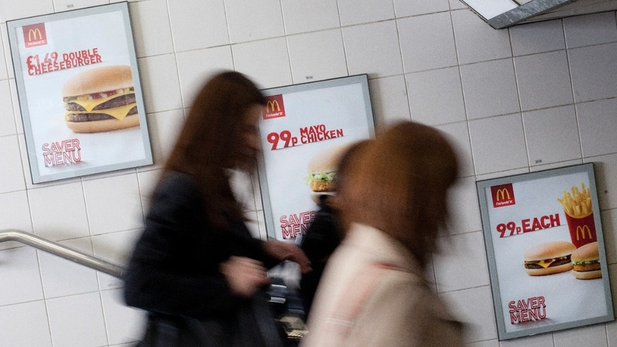 April 30, 2012: Three women walk past an advert for McDonald's fast food restaurant products in London.